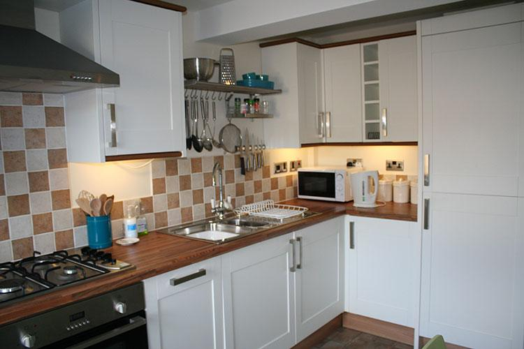 The Corwn Apartment kitchen with microwave and gas hob