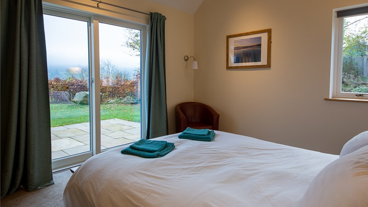 Master bedroom with large patio doors to the garden and lovely views