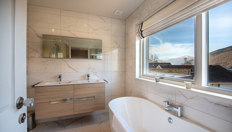 Beautiful master en-suite bathroom with freestanding bath, his and hers sinks and large shower cubicle