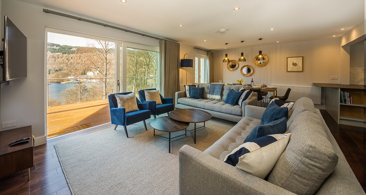 Living space with large patio doors opening on to decked balcony