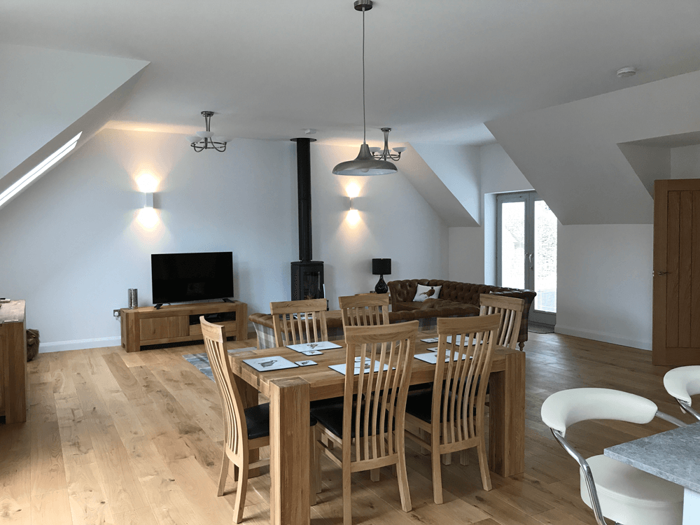 Saorsa open plan living and dining area with balcony overlooking Loch Tay in the Scottish Highlands